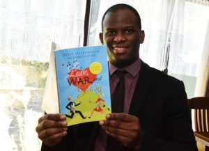 Denis smiling & holding a copy of his spoken word collection