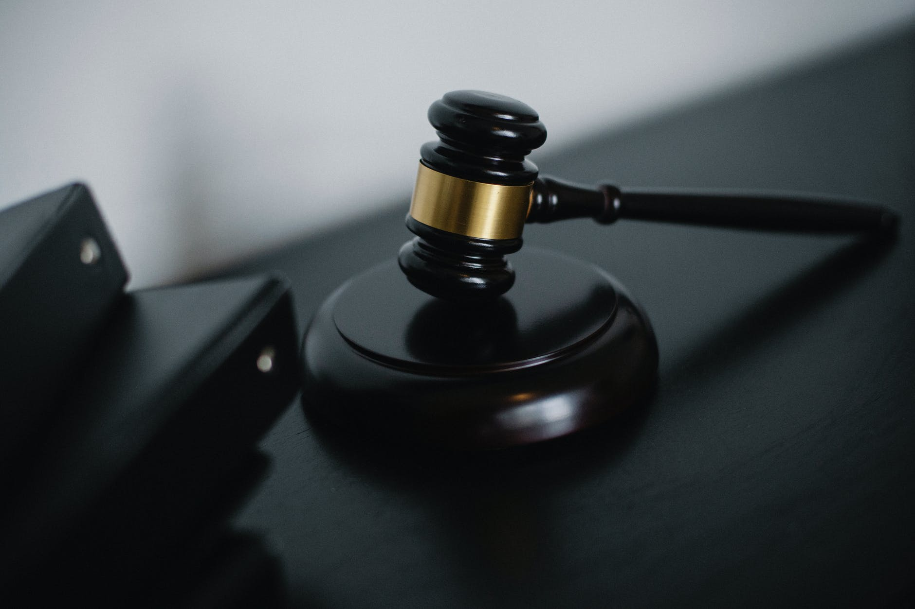 small judge gavel placed on table near folders